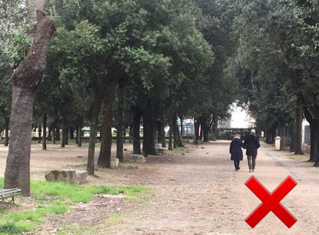 Una coppia passeggia per Villa Borghese mano nella mano. Sbagliato.
