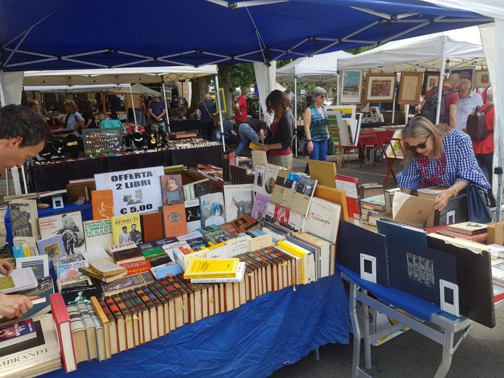 Quadri, libri e oggetti vintage sui banchi del mercatino allestito sul piazzale di Porta Pia