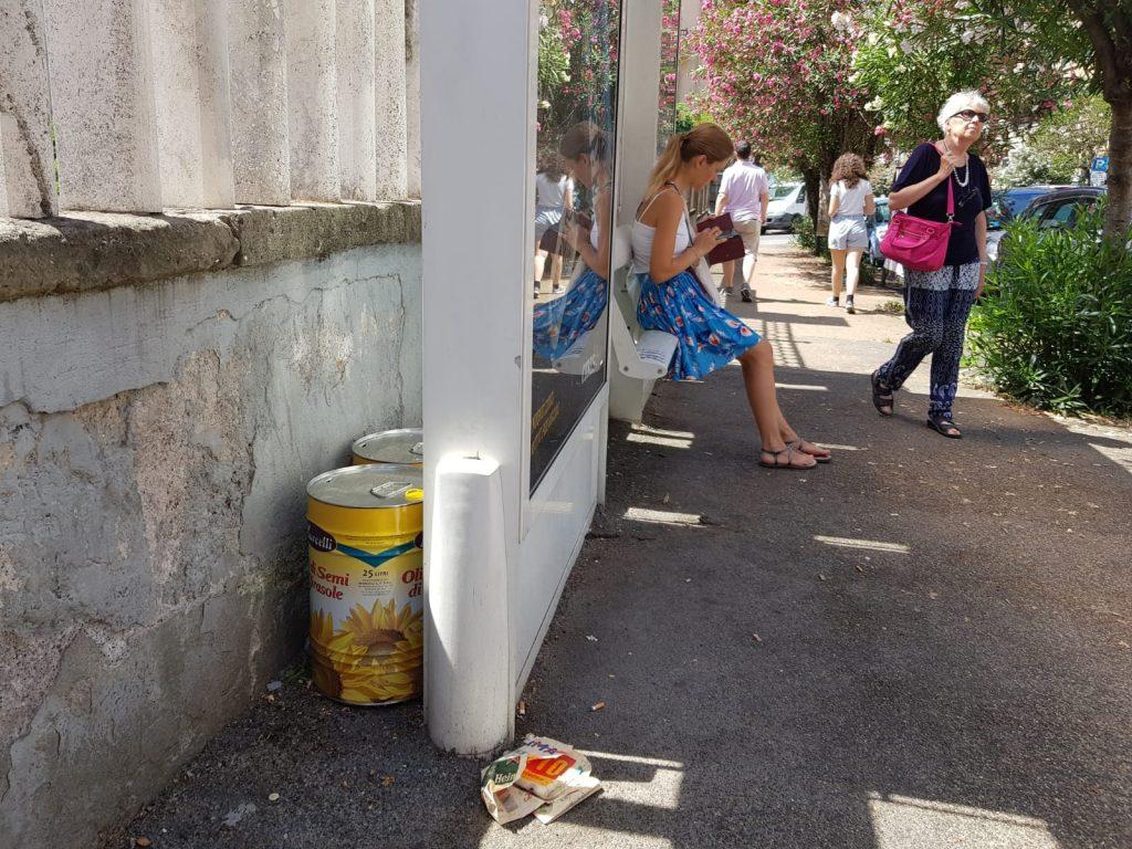 Le due latte d'olio abbandonate dietro la fermata dell'autobus in via Nemorense