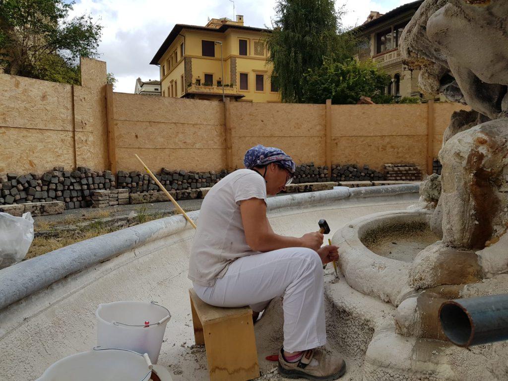 Una delle responsabili del restauro al lavoro dentro alla fontana