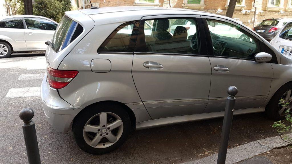 Un'auto parcheggiata a via Lariana davanti alla rampa di accesso per disabili